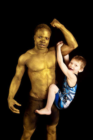 a man painted gold showing off his strength by holding up a young boy by his bicept. photo