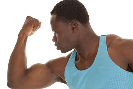 A man in hisblue tank looking down at his flexed arm with a serious expression on his face. photo