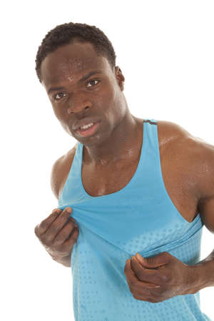 A man holding on to his blue tank that is wet from sweat. photo