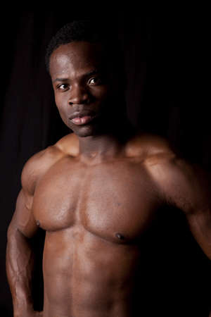 a man standing on a black background showing off his muscled body. photo