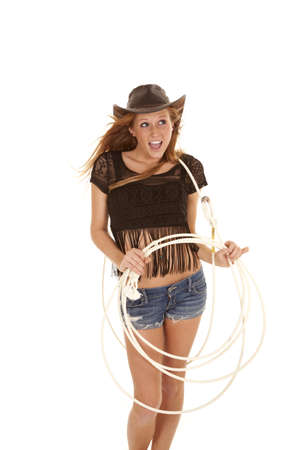 A cowgirl having some fun with her rope with the wind blowing in her hair photo