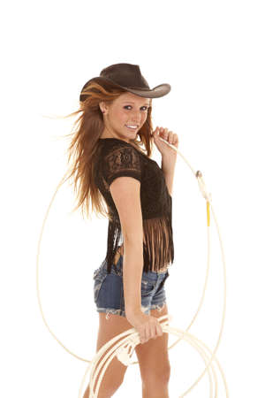 A cowgirl holding a rope  with a huge smile on her face. photo