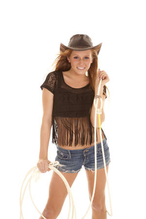 A cowgirl holding on to her rope with a smile on her face. photo