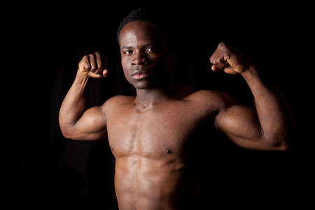 A man flexing his muscles on a black background. photo
