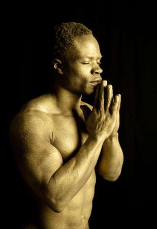 body paint: Un hombre pintado de oro orando sobre un fondo negro