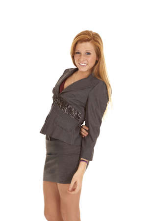 A red headed women standing in her business clothes with a smile on her face Stock Photo