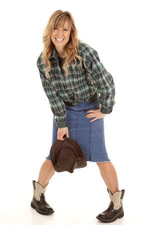cowgirl hat: Una mujer con las piernas flexionadas con su sombrero de vaquera sonriendo y riendo. Foto de archivo