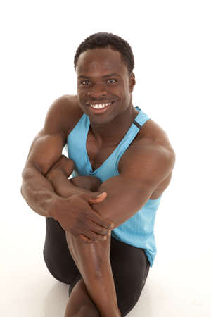 A man stretching out his leg with a smile on his face. photo