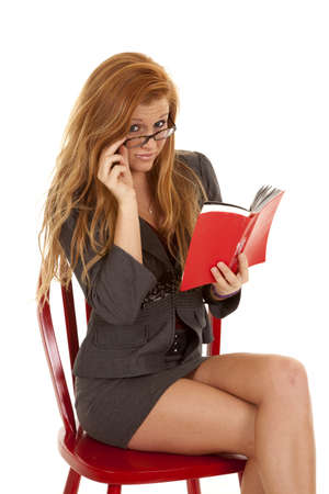a woman sitting on a red chair wearing glasses and reading  a book. photo