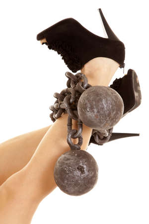 A woman with ball and chain wrapped around her ankles while she is wearing her high heels. photo