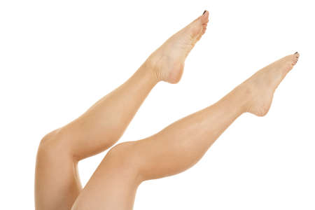 A woman with just her legs up in the air pointing her toes.