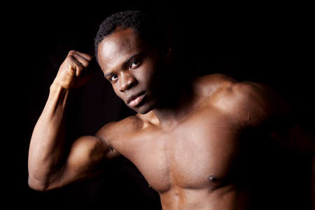A man on a black background looking at the camera showing off his muscles. photo