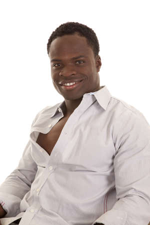 shirt unbuttoned: A man sitting with a smile on his face with his shirt unbuttoned. Stock Photo