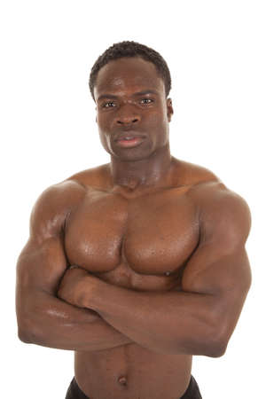 A man standing with his arms folded across his body showing off his muscles Stock Photo