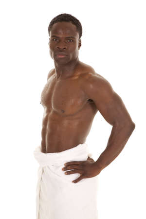 An African American wet and standing with a serious expression on his face with a white towel wrapped around his waist. photo