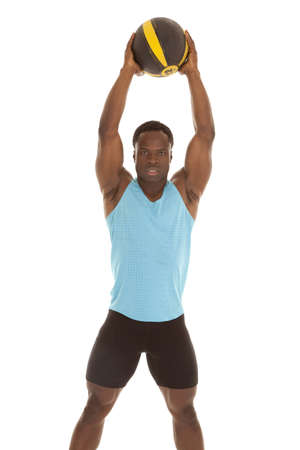 A man holding up his medicine ball up in the air with a serious expression  on his face photo