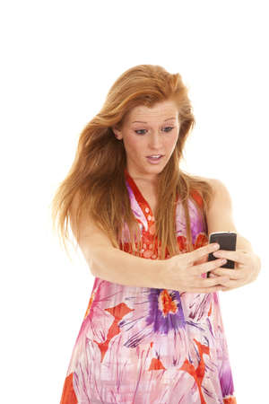 A woman with a surprised expression on her face reading a text photo