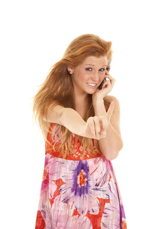 a woman talking on the phone with her finger out telling someone to wait. photo