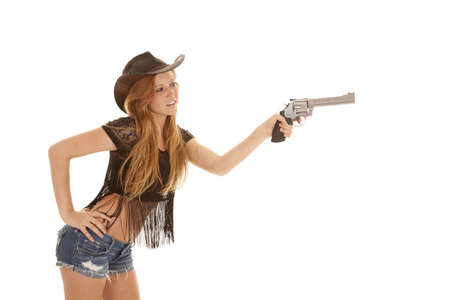 A woman pointing her gun to the side while wearing her cowboy hat. photo