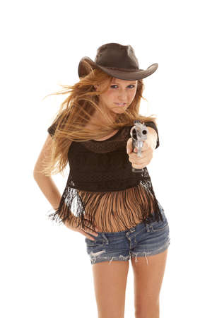 a woman standing and pointing her gun at the camera with the wind blowing her hair. photo