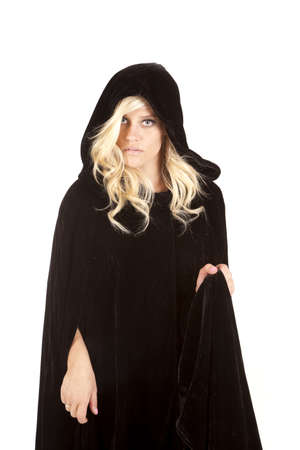 a woman wearing her black cape with a serious expression on her face.
