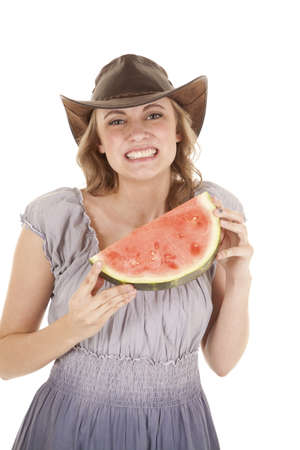 A woman holding on to her watermelon with  a smile on her face. photo
