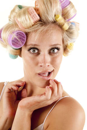A woman with curlers in her hair and her hands by her face. photo