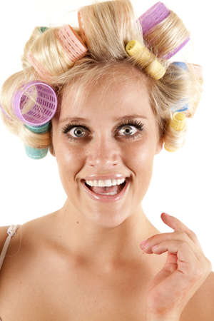 A woman has curlers in her hair and is smiling. photo