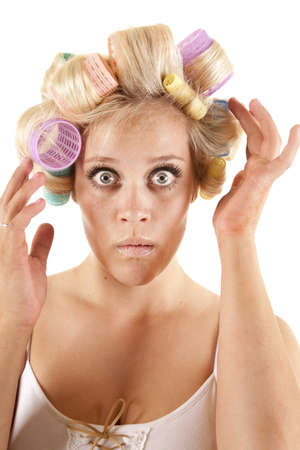 A woman is touching the curlers in her hair. photo