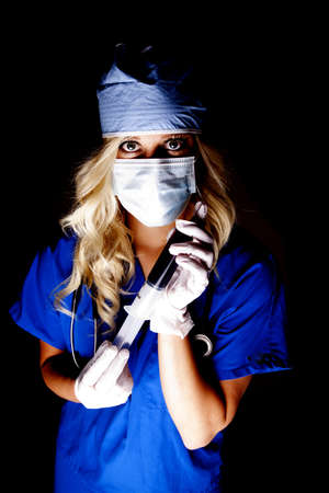 A woman doctor with a big needle full of blood in the dark. Stock Photo - 14611526
