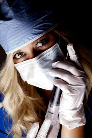A close up of a female doctor with a huge needle. Stock Photo - 14611539