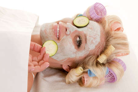 A woman has curlers in her hair and a cream face mask holding a cumber slice. photo
