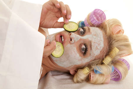 A woman has curlers in her hair and a cream face mask holding a cumber slice. 免版税图像