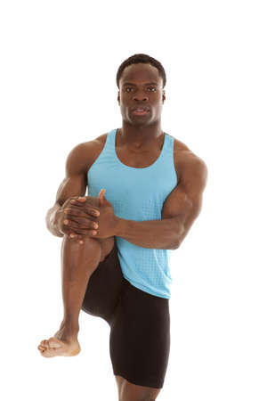A man stretching his leg with a serious expression on his face. photo