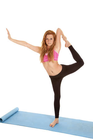 A woman pulling her leg up to stretch with a serious expression on her face. photo