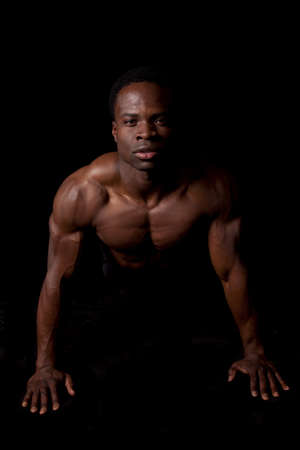 push: A man doing a push up showing off his muscles on a black background.