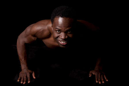 A man doing a push up showing off his muscles on a black background. photo