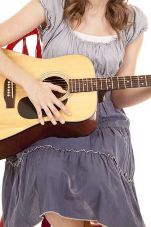 A close up of a woman playing her guitar while sitting on a red chair. photo