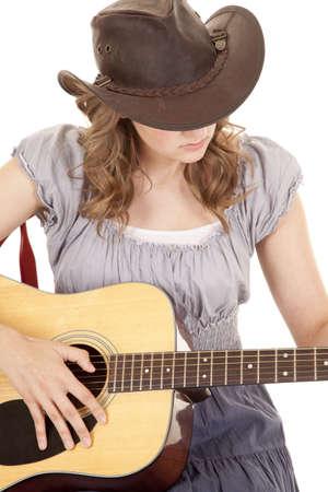 cowgirl hat: Una mujer sentada con su sombrero de vaquera en tocar la guitarra.