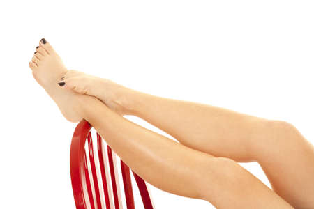 A woman relaxing  and putting up her bare feet and legs up on the back of a red chair. photo