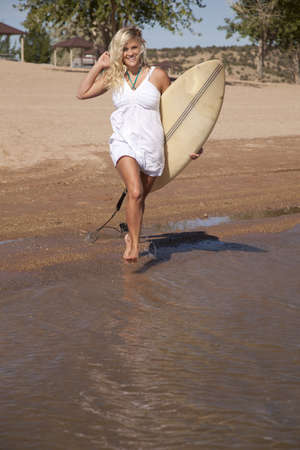 A woman holding on to her surf board walking into the water from the beach. photo