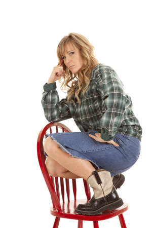 A woman with her  red boots on a chair with a serious expression on her face. photo