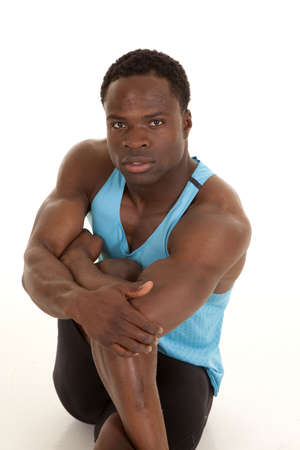 A man stretching out his leg with a serious expression on his face photo