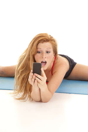 A woman with a shocked expression looking at her phone while she is stretching. photo