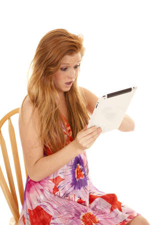 a woman shocked at what she is looking at on her tablet photo