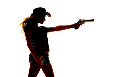 a silhouette of a woman holding out a pistol. photo