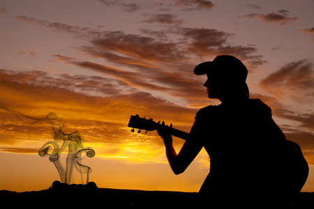 A woman is sitting with a guitar in the sunset by a camp fire. photo
