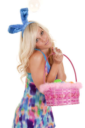 A woman dressed like an easter bunny has a basket of eggs. photo