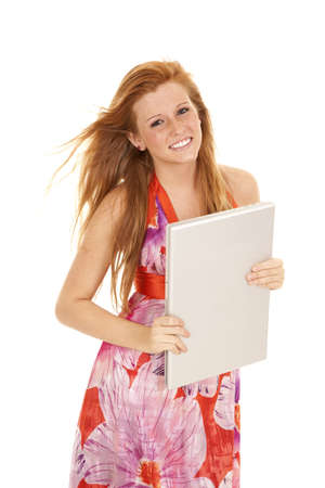 A woman holding on to her laptop with a smile on her face while the wind is blowing her hair. photo