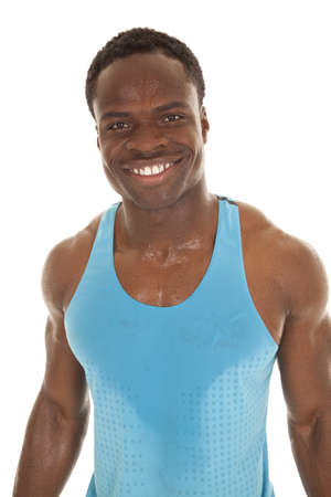 A man with sweat on his shirt and body with a big smile on his face. photo